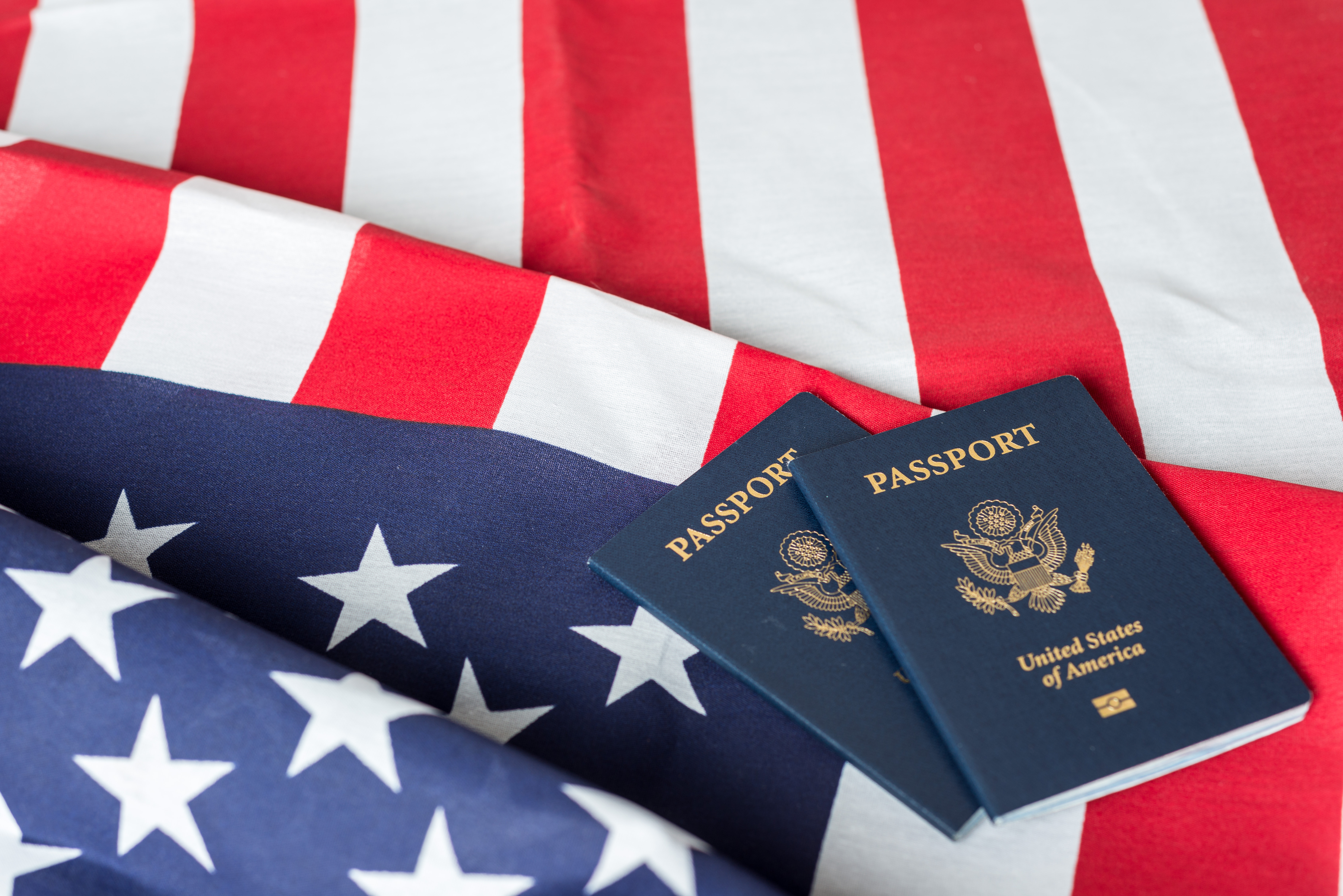 Флаг и паспорта США, гражданство которых могут получить иностранцы