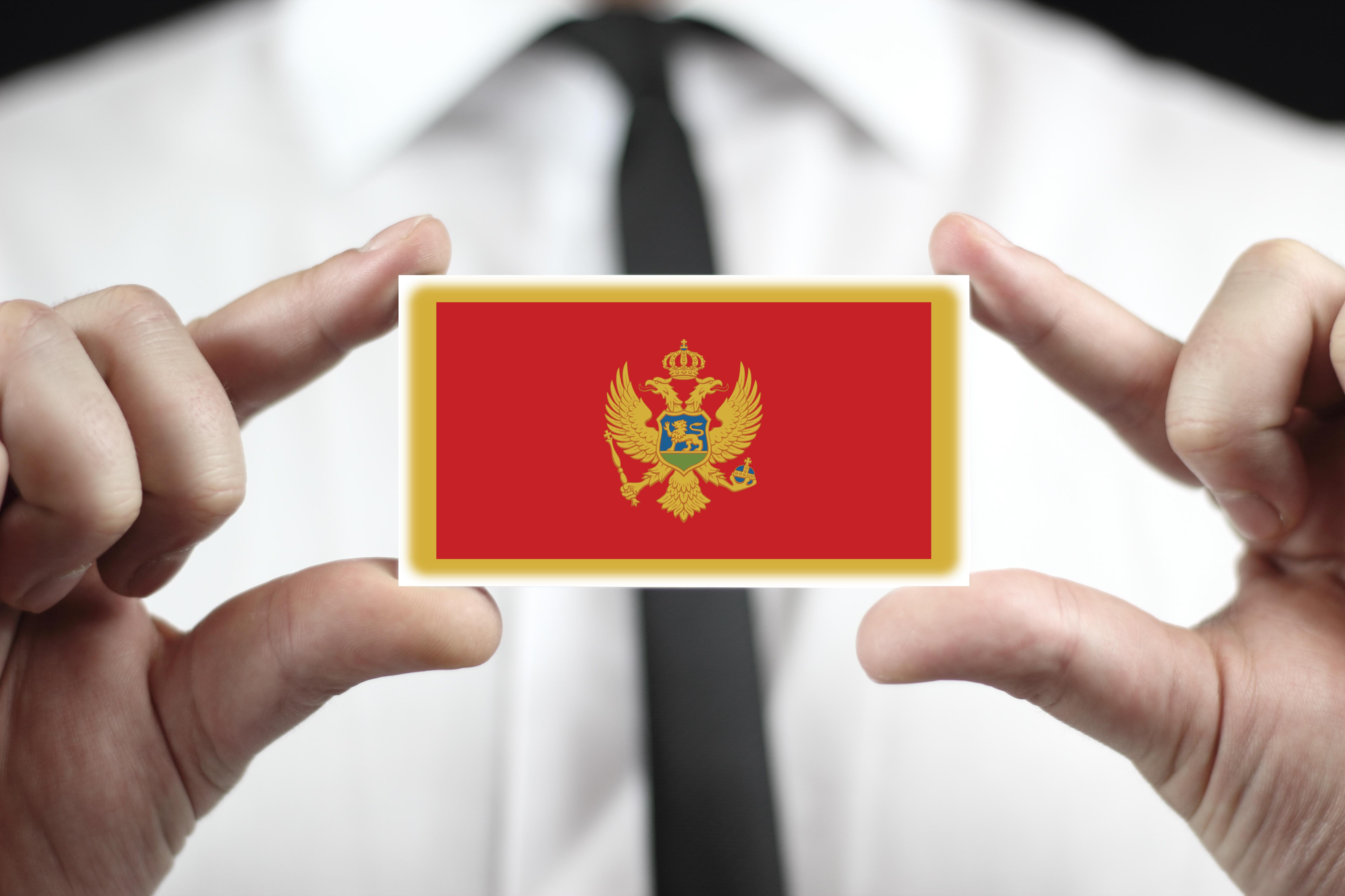 Бизнес-иммигрант держит флаг Черногории, получить ВНЖ которой можно через открытие фирмы